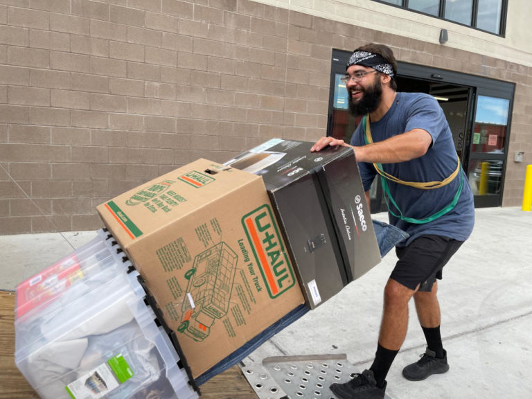 Aaron Movers employee hauling boxes up truck ramp with a dolly