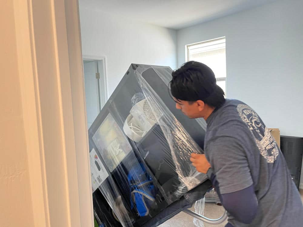 Aaron Movers employee moving a dresser