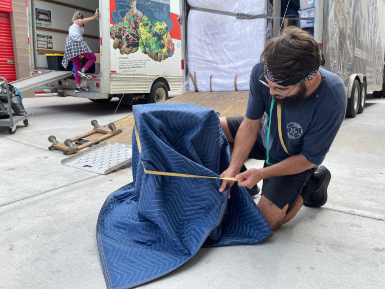 Aaron Movers employee wrapping item in protective blanket